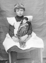 Child-wearing-a-pinafore_and_Doll_Sept0214wiki-sized