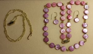 Grati's jewelry--gold initial necklace, and flat pink beads gold necklace and earrings