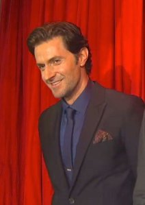Richard Armitage smiling in front of red curtain at 2013 THDofS Berlin premiere.