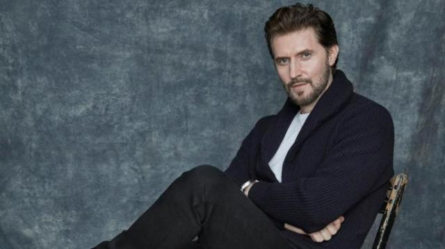 Richard Armitage sitting in chair; portrait via An Le