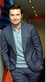 RAPortrait--2017x--RichardArmitage-leaning-&smiling-in-blue-gray-plaid-suit-and-ltbl-sweater_Aug21-2021viaSimonne