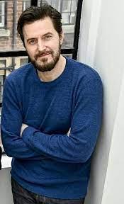 RAPortrait--2020x--RIchardArmitage-bearded-longer-hair-in-blue-sweater-next-to-window_June01-2021viaPinterest-viaGrati